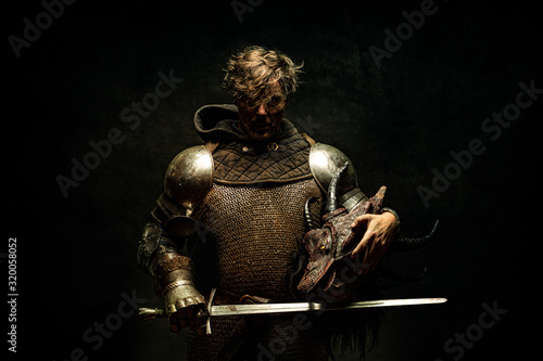 Photo Portrait of a knight in armor, his sword in his hand, holding a dragon head in t
