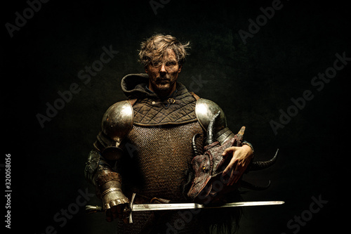 Portrait of a knight in armor, his sword in his hand, holding a dragon head in t Fototapete