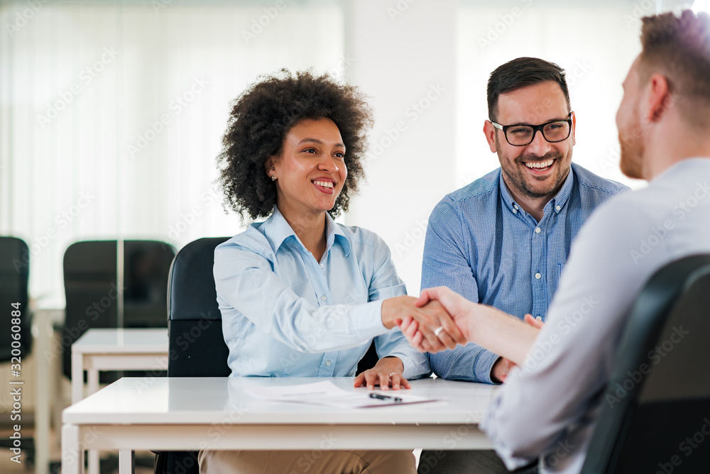 Fototapeta Smiling HR managers handshake with a job candidate.