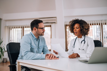 Doctor talking to a patient at medical clinic.