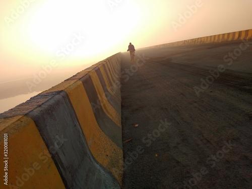 Carta da parati Rear View Of Man Cycling On Bridge Against Sky During Sunset