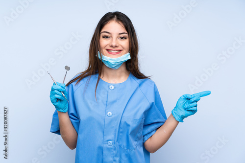 Woman dentist holding tools over isolated blue background pointing finger to the side