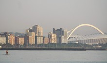 Man Paddleboarding In Sea By Moses Mabhida Stadium In City Against Clear Sky