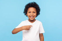 This Is Me. Portrait Of Happy Preschool Curly Boy In T-shirt Joyfully Looking At Camera And Pointing To Himself, Proud Of Own Success, Egoistic Child. Indoor Studio Shot Isolated On Blue Background