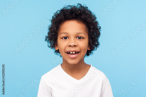 Obraz Closeup portrait of amazing cheerful little boy with curly hairdo in white T-shirt looking at camera with happy carefree smile and missed milk teeth. indoor studio shot isolated on blue background - fototapety do salonu
