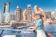 Cheerful Girl Traveler On A Ferry Boat Sailing Through Dubai Marina Port Among Huge Skyscrapers. Concept Of Tourism In The UAE