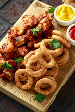 Sticky Glazed Chicken Wings And Deep Fried Battered Onion Rings Served With Lemon Wedges, Tomato Ketchup And Mustard. Greasy, Fast Food Concept