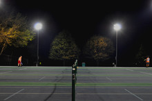 Players At Tennis Court At Night