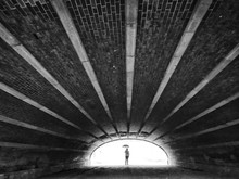 Mid Distance View Of Person Holding Umbrella Seen From Tunnel