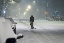Man Riding Bicycle On Snow Covered Road At Night