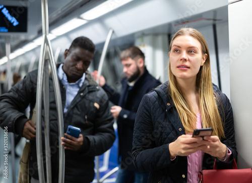 Fototapety, obrazy: Girl using mobile phone in metro car