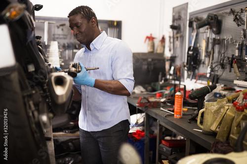 Confident worker examines a broken motorcycle part of the working area Wallpaper Mural