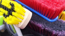 HIGH ANGLE VIEW OF MULTI COLORED BROOMS