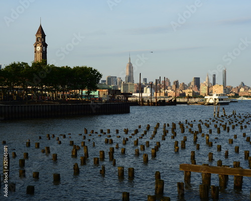 Платно Wooden Posts In River By Clock Tower And Empire State Building Against Sky