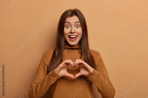 Photo Portrait of lovely joyful woman shapes heart gesture over chest, expresses love and sympathy to boyfriend, has funny expression, long dark hair, dressed in brown turtleneck
