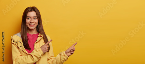 Positive attractive girl points at upper right corner and recommends something, advertises promotion, smiles pleasantly, wears yellow windbreaker, shows interesting place to visit, suggests advert