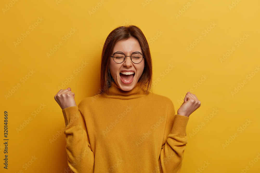 Fototapeta Overjoyed brunette young lady clenches two fists, celebrates success and exclaims with joy, shouts good job, makes hooray gesture, triumphs from successful deal or awesome news, feels thrilled