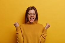 Overjoyed Brunette Young Lady Clenches Two Fists, Celebrates Success And Exclaims With Joy, Shouts Good Job, Makes Hooray Gesture, Triumphs From Successful Deal Or Awesome News, Feels Thrilled
