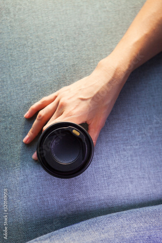 Young woman holding disposable coffee cup Wallpaper Mural