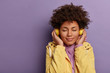 Horizontal shot of lovely woman meloman uses electronic headphones, feels enjoyment and pleasure from popular sound track, closes eyes, wears yellow anorak, isolated on purple wall, copy space