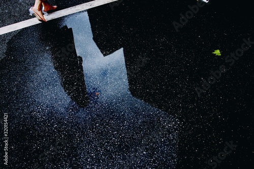 Fotografia Reflection of woman and buildings in puddle on street
