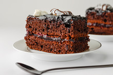 Dessert Concept. Sweet Slice Of Chocolate Cake On White Background. Close Up