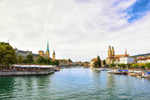 Limmat River Quay With Boats And Three Main Churches Of Zurich - Grossmunster, Fraumunster And St Peter Church, In Switzerland