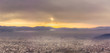 Panoramic view of misty Pirot cityscape covered by first winter snow and stunning golden sunset colors in the sky