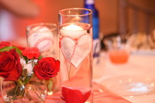 Close-Up Of Candles By Red Roses In Vase On Table