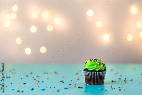 Photo green frosting single cupcake with icing and sprinkles