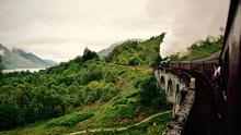 Train On Bridge Leading Towards Green Mountain Against Cloudy Sky