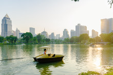 Man Riding On Paddle Boat Over Lake By City Against Clear Sky