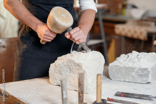 Bearded craftsman works in white stone carving with a chisel Fototapet