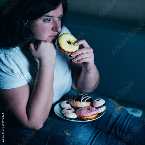 Fotomural Overweight depressed woman laying on sofa eating sugary food watching TV