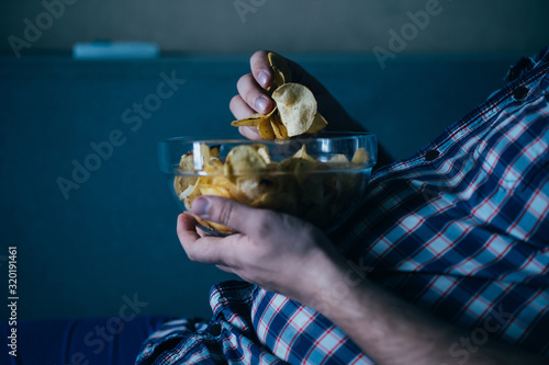 overeating, sedentary lifestyle, bad habits, food addiction, eating disorders. fat overweight man lay on the coach with tv remote and junk food. depression, laziness