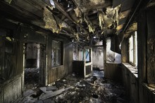 Inside Shot Of An Abandoned Destroyed Building With Burned Walls And Worn-out Doors