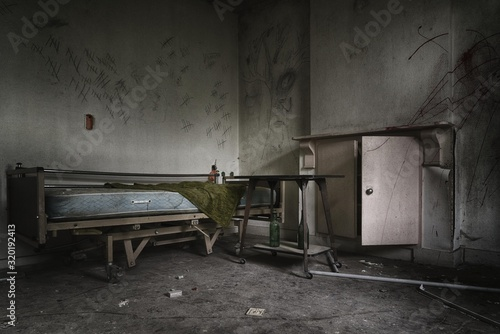 Dramatic shot of an abandoned prison room with a broken bed and weathered window Canvas Print