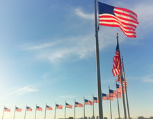 Low Angle View Of American Flags Against Blue Sky