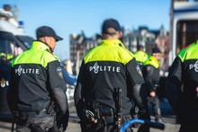 """Dutch Police Squad Formation And Horseback Riding Mounted Police Back View With """"Police"""" Logo Emblem On Uniform Maintain Public Order After Football Game And Rally In The Streets Of Amstrdam Center"""