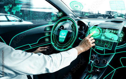 obraz dibond Self-driving autonomous car with relaxed young man sitting at driver seat is driving on busy highway road in the city. Concept of machine learning, artificial intelligence and augmented reality.