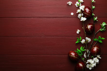 Easter Eggs And Spring White Flowers On Easter Red Wood Background With Copy Space