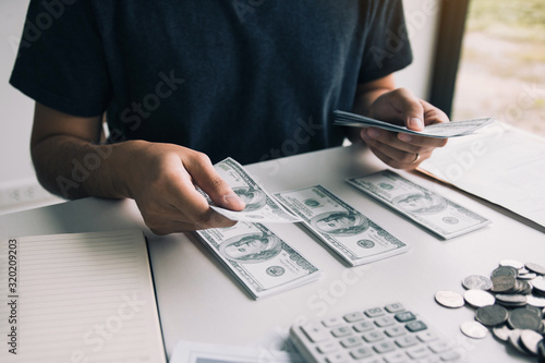 Fototapeta Asian men are holding banknotes in cash and placed on the table with the idea of saving money. obraz