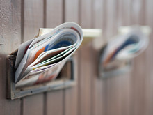 Close-Up Of Folded Newspapers In Mail Slots Of Closed Door
