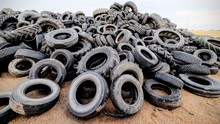Heap Of Damaged Tires On Field