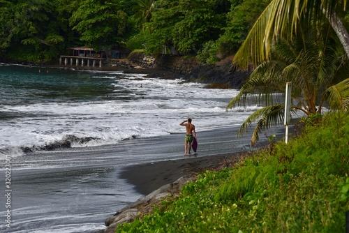 Fototapeta Lone, male surfer walking along a black sand beach in Tahiti.