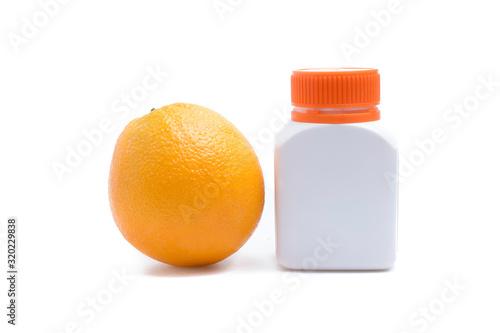 Photo Orange fruit with tablets bottle on white background.
