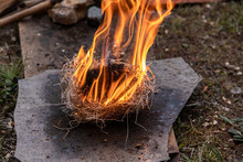 Flame Burning Using Straw As Fire Starter On Grey Slate During Demonstration Of Native Traditional Way For Natural Fire Lighting During World Festival