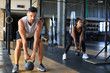 Leinwanddruck Bild - Fit and muscular couple focused on lifting a dumbbell during an exercise class in a gym.