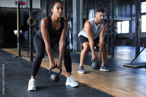 Fit and muscular couple focused on lifting a dumbbell during an exercise class in a gym Fototapete