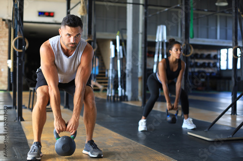 mata magnetyczna Fit and muscular couple focused on lifting a dumbbell during an exercise class in a gym.